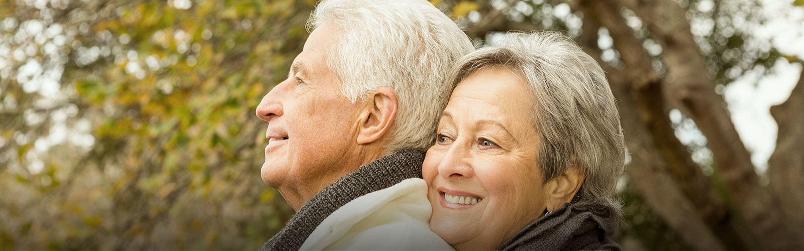 Elderly couple hugging and smiling outdoors
