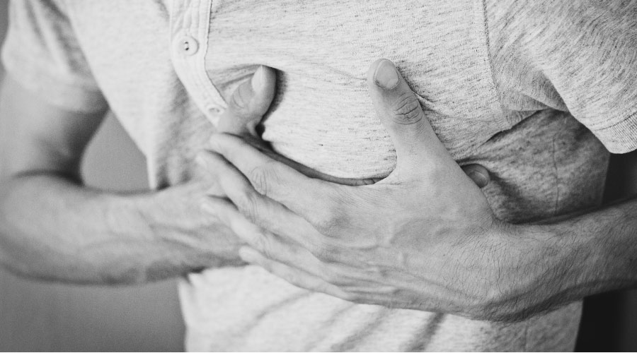 man holding his chest with acid reflux and heartburn