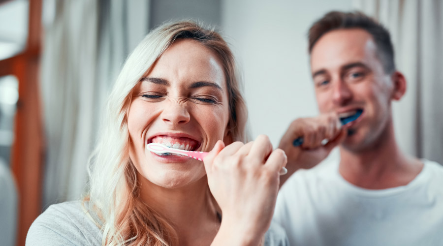 Woman & man in the background brushing their teeth to eliminate the risk of cavities