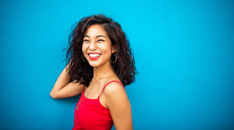 Brunette woman in a red tanktop smiles against a blue wall because she is pain-free after root canal therapy