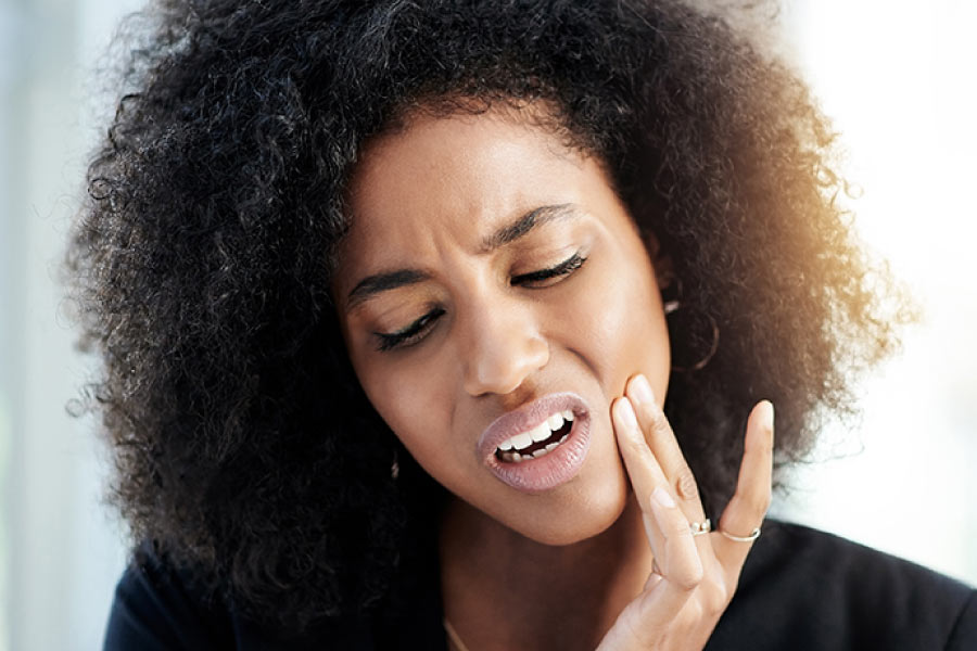 Young black women with her hand to her jaw and a pained expression on her face indicating a toothache