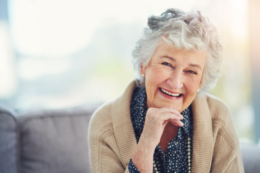 Smiling white haired elderly woman in a tan sweater resting her chin on her hand