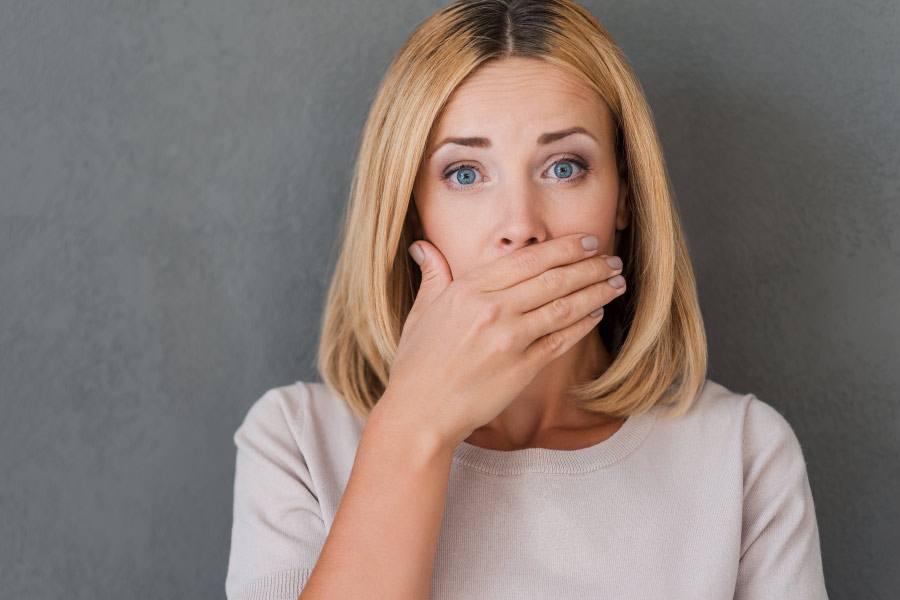 Blonde woman covers her mouth due to fear of bad breath or halitosis.