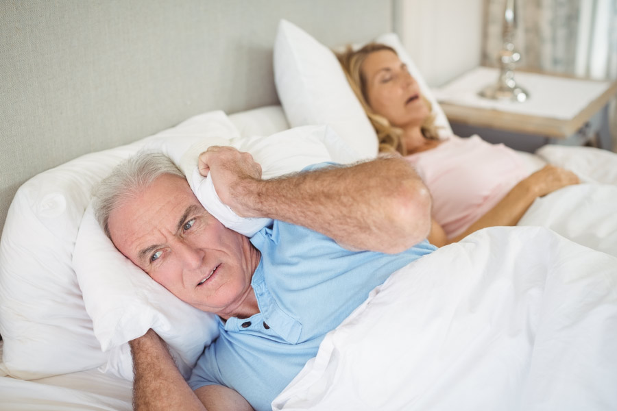Man holds a pillow over his ears while his wife snores because of sleep apnea.