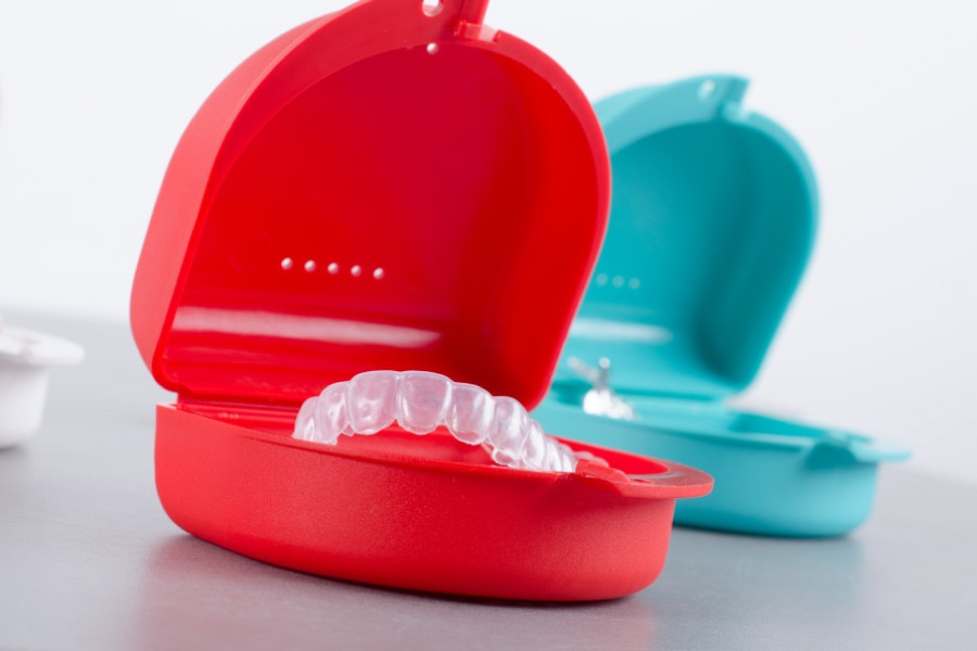 Colorful cases filled with Invisalign clear aligners.